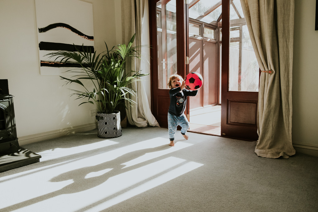 baby boy running with a ball in the living room
