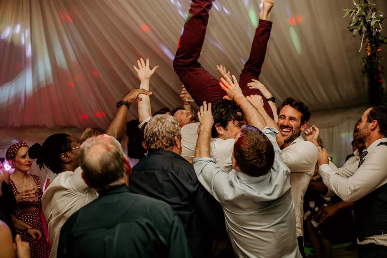 groom carried on shoulders by groomsmen during his Scotland elopement