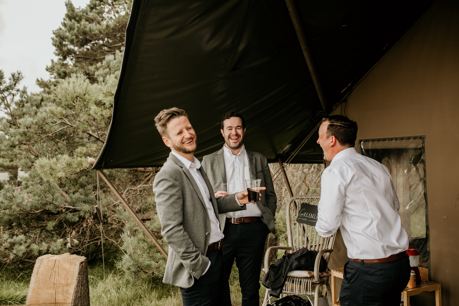 groomsmen laughing outside the tent at Harvest Moon Holidays Scotland