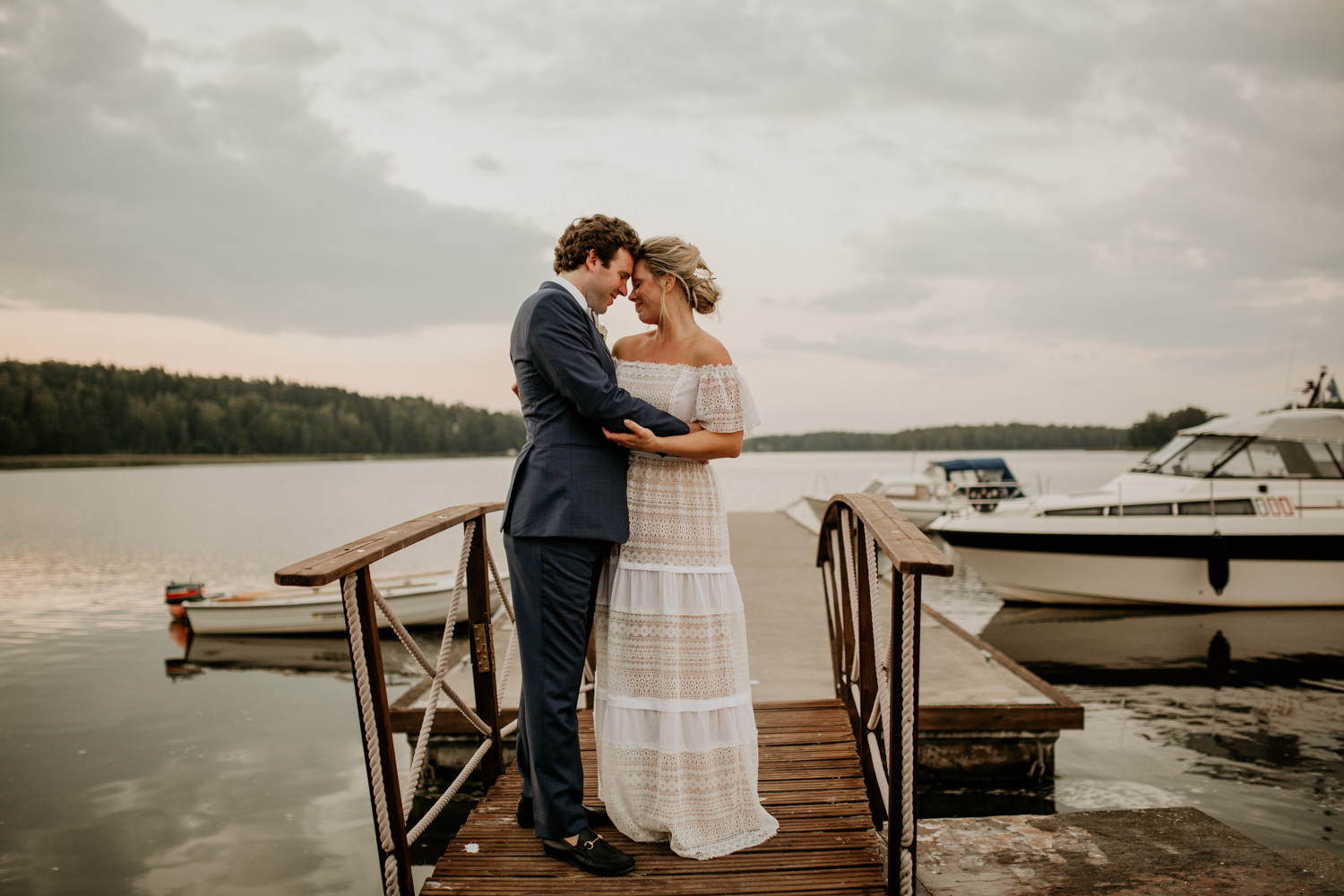 bride and groom touch foreheads on the dock by Finland wedding photographers