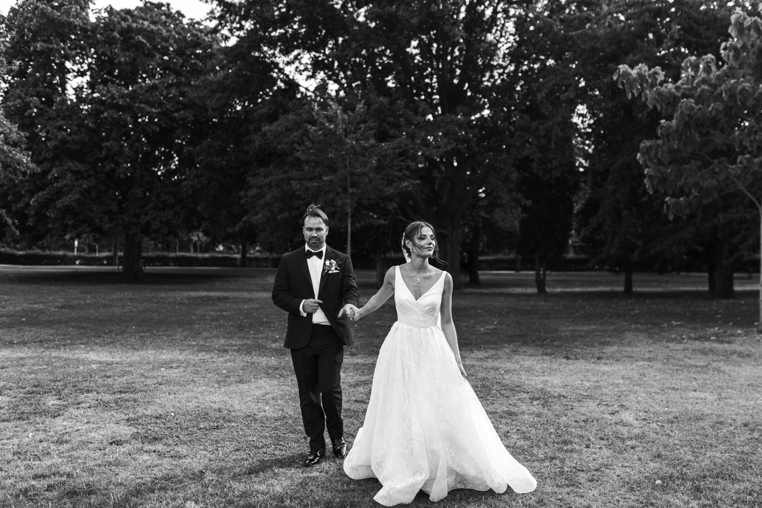 black and white image of bride and groom walking holding hands during their wedding portraits