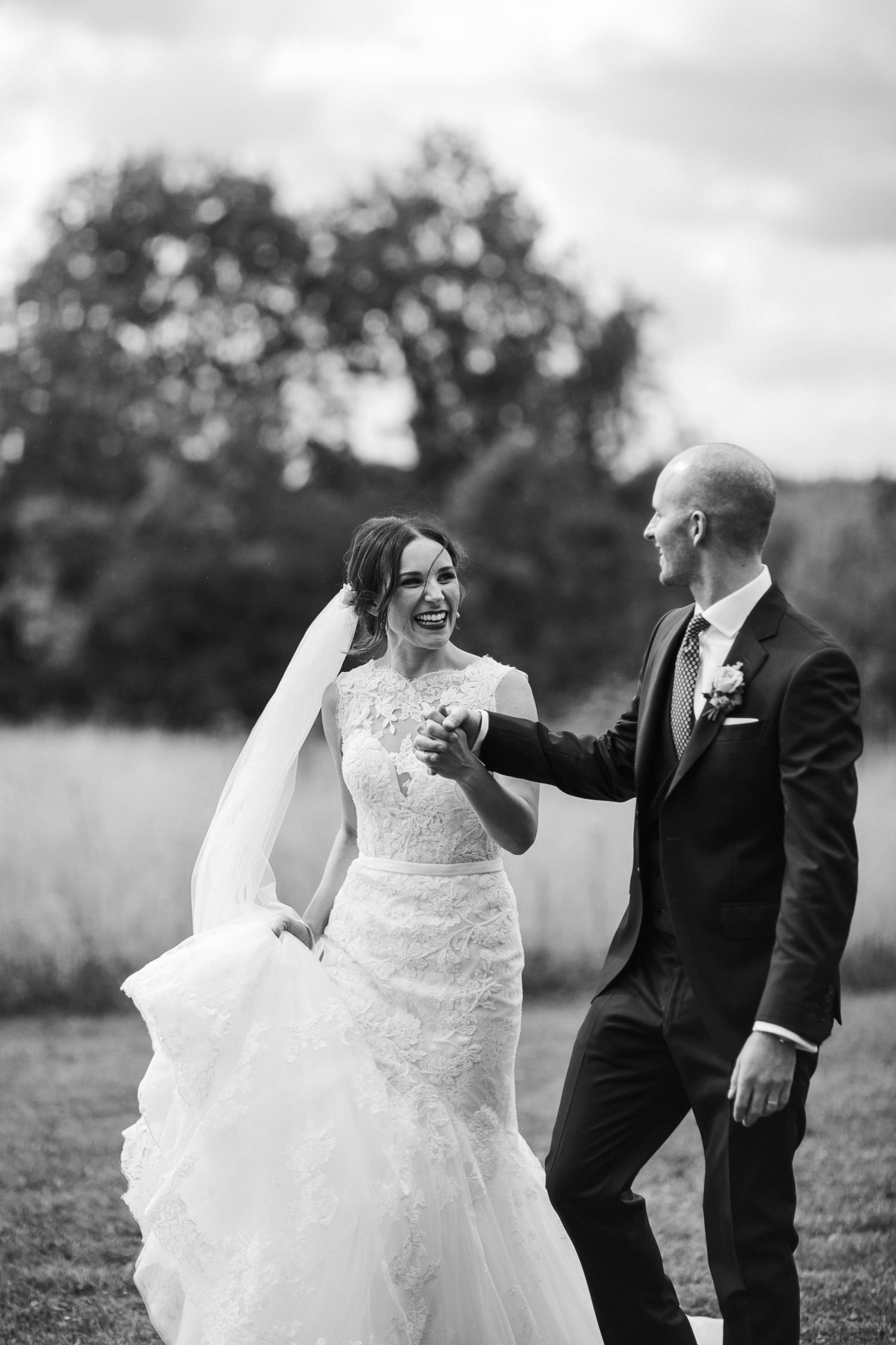 black and white image of bride and groom holding hands during their Merriscourt wedding barn wedding