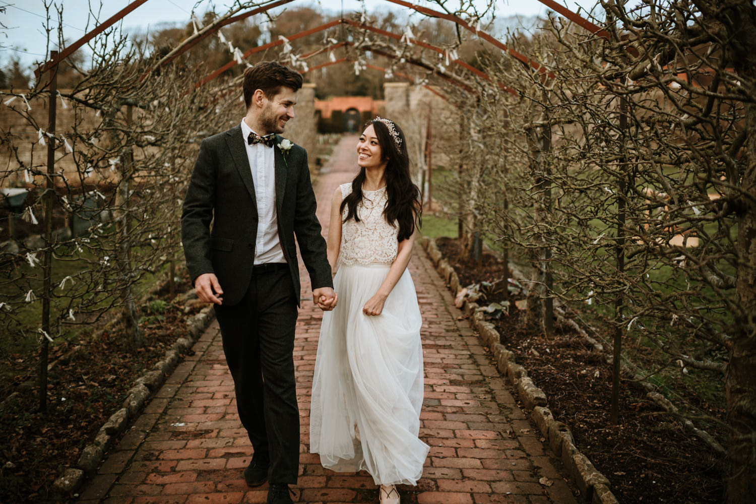 bride and groom walking and holding hands during their wedding portrait shoot