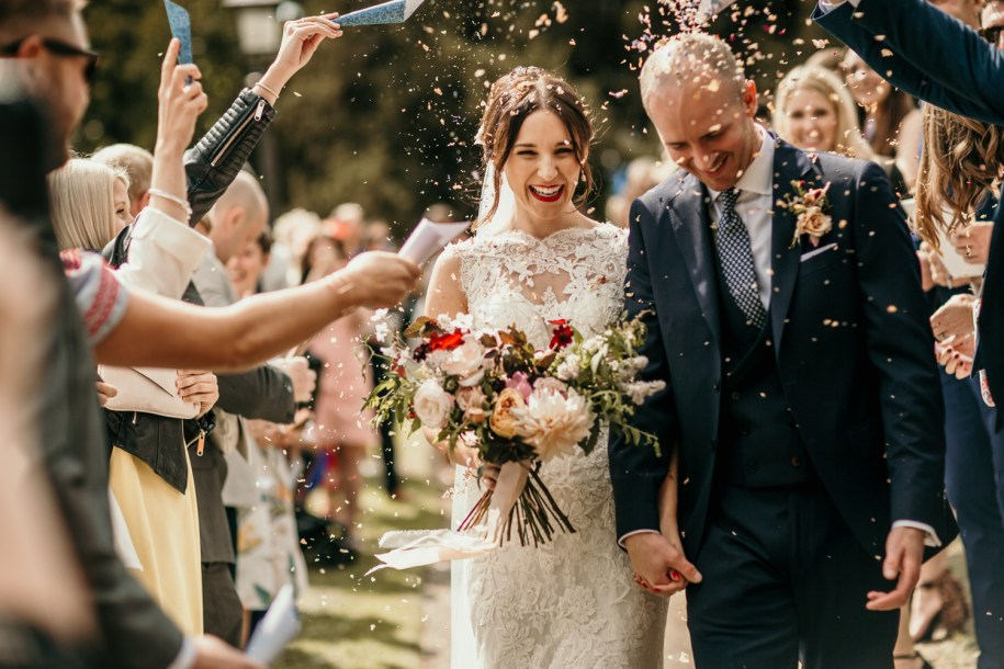 bride and groom during confetti holding bohemian wedding flowers