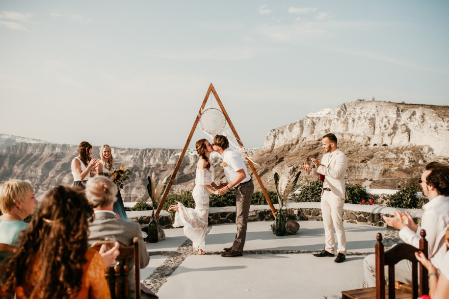first kiss during the outdoor wedding ceremony in Greece