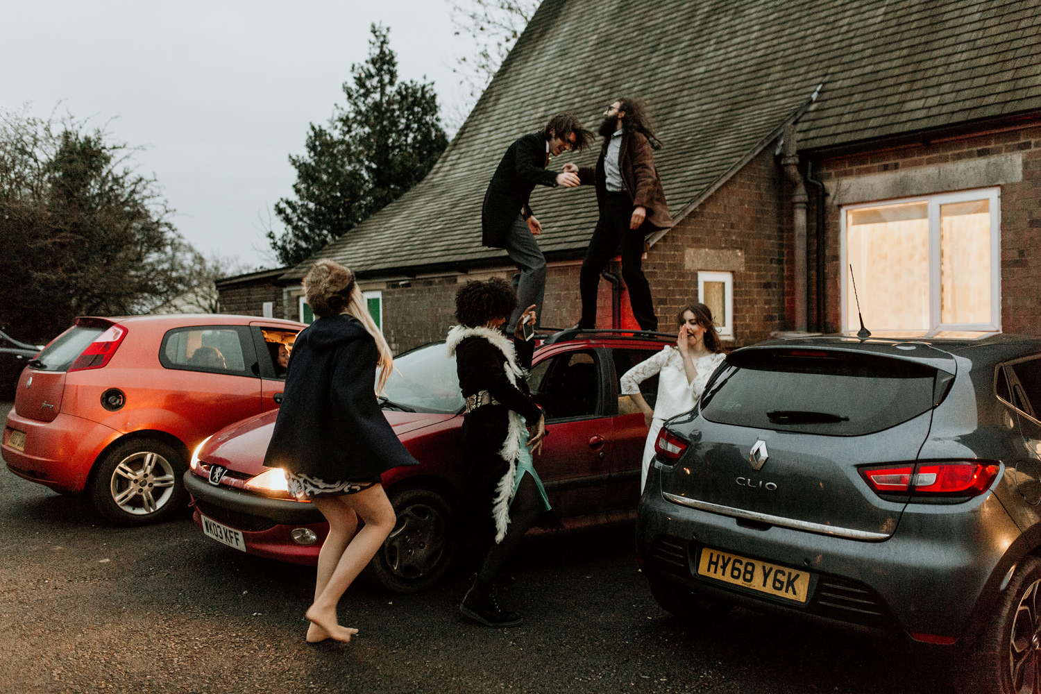bride and friends dancing on a car after their wedding in Stroud