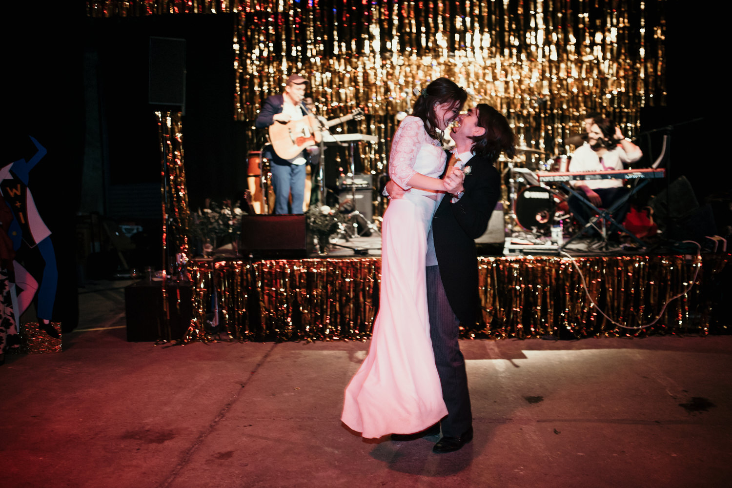 bride and groom during their first dance with Josh Flowers playing on the stage