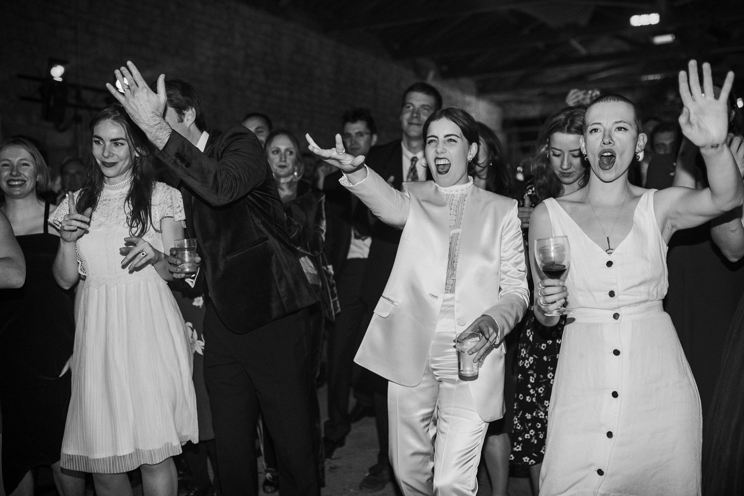 bride wearing a white suit and guests dancing for their stround wedding