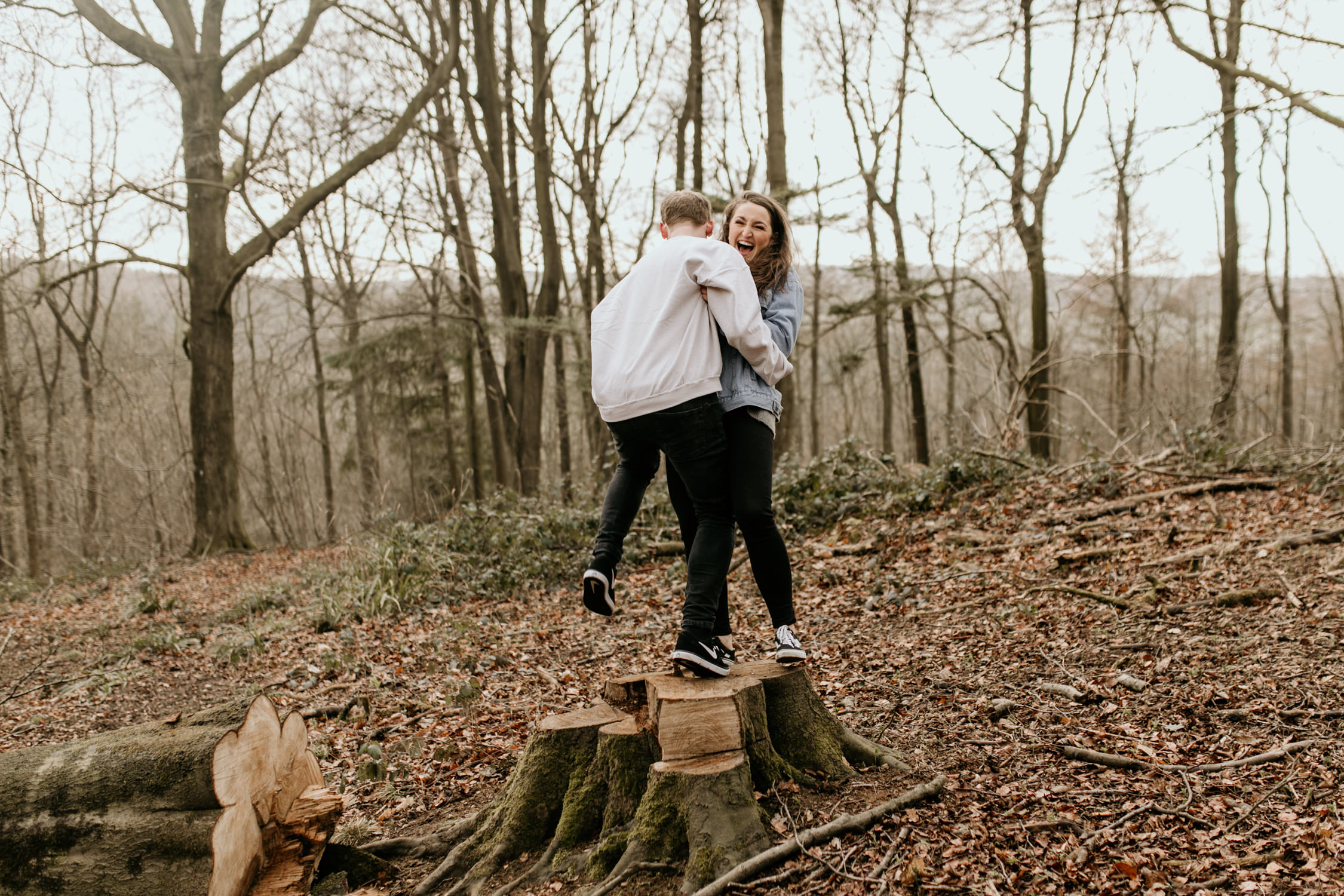 couple jumping into each other arms during their engagement session at Broadway Tower by Cotswolds photographer