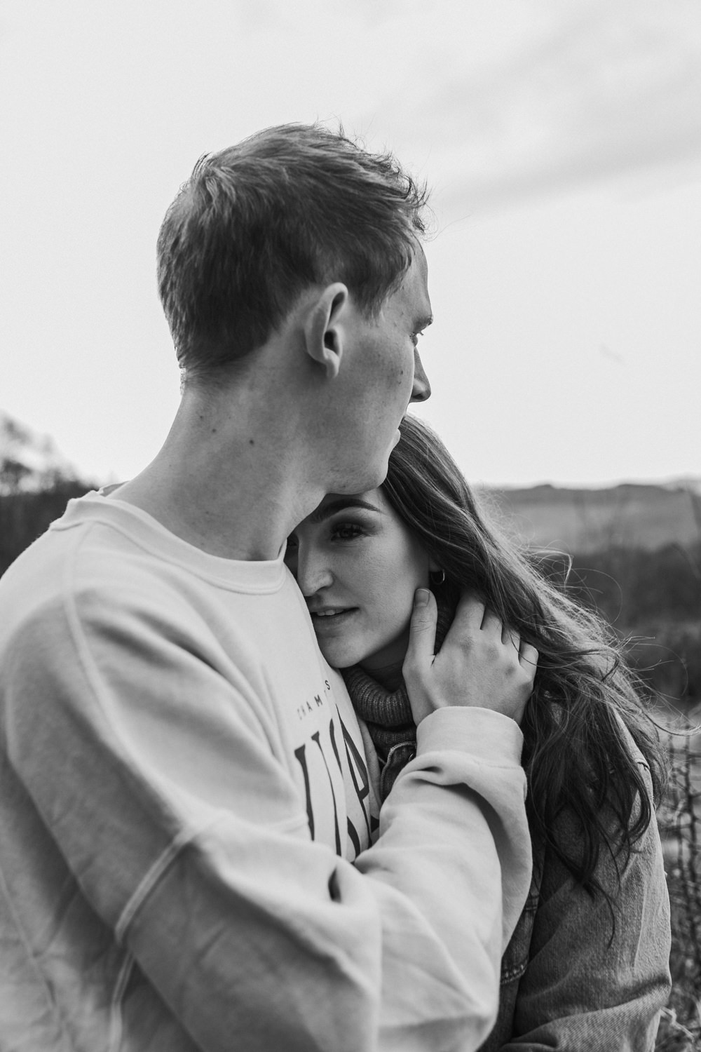 beautiful black and white image of guy embrace girl during their engagement shoot at Broadway Tower in the Cotswolds countryside