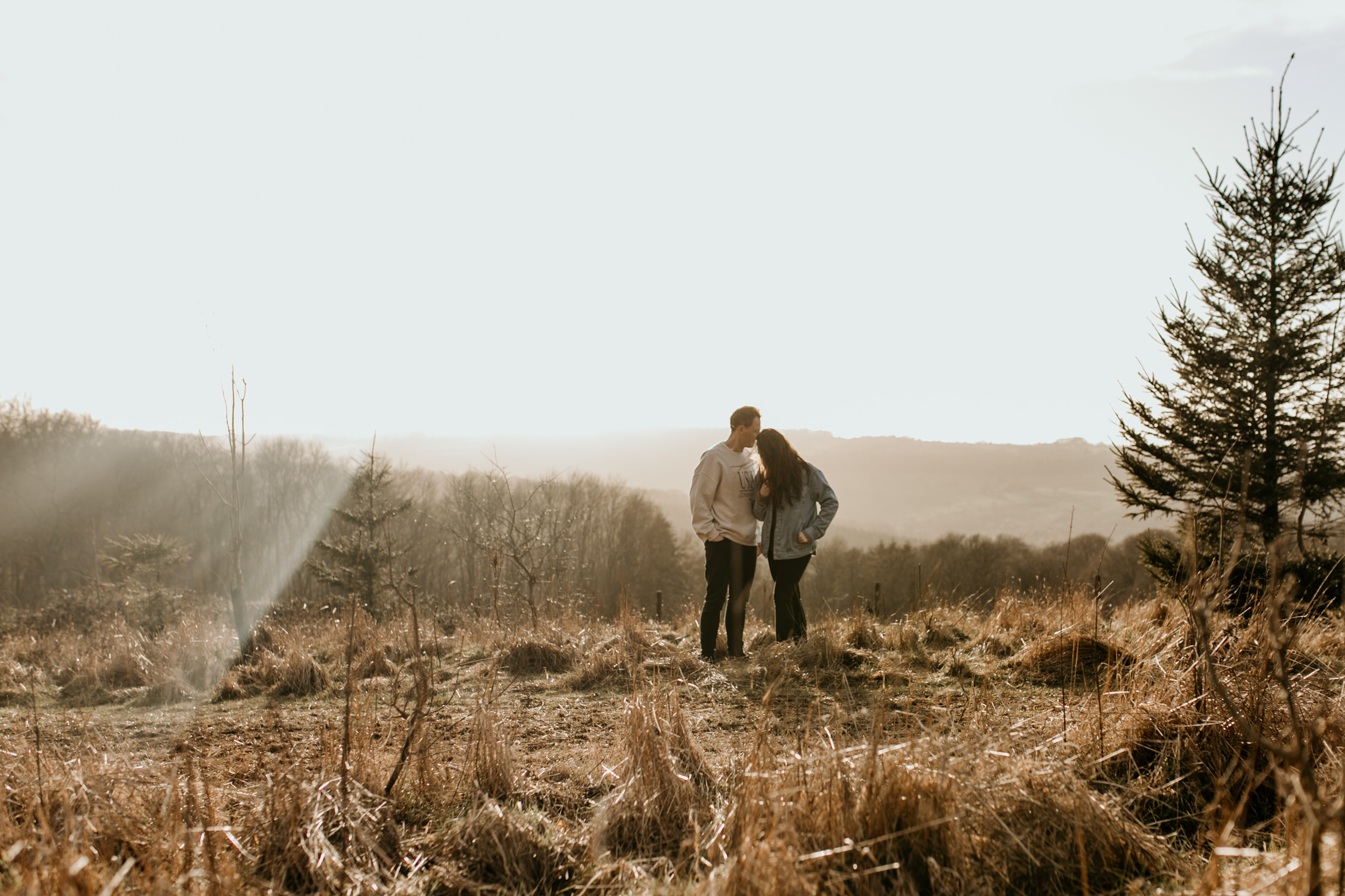 wide portrait of couple during their engagement session in the Cotswolds on the fields of Broadway Tower
