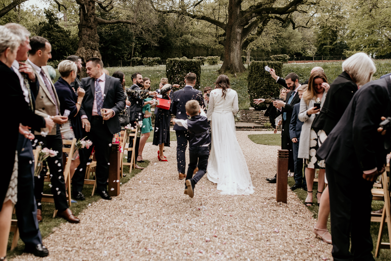 little boy throwing confetti behind bride and groom at Coombe Lodge Blagdon wedding venue