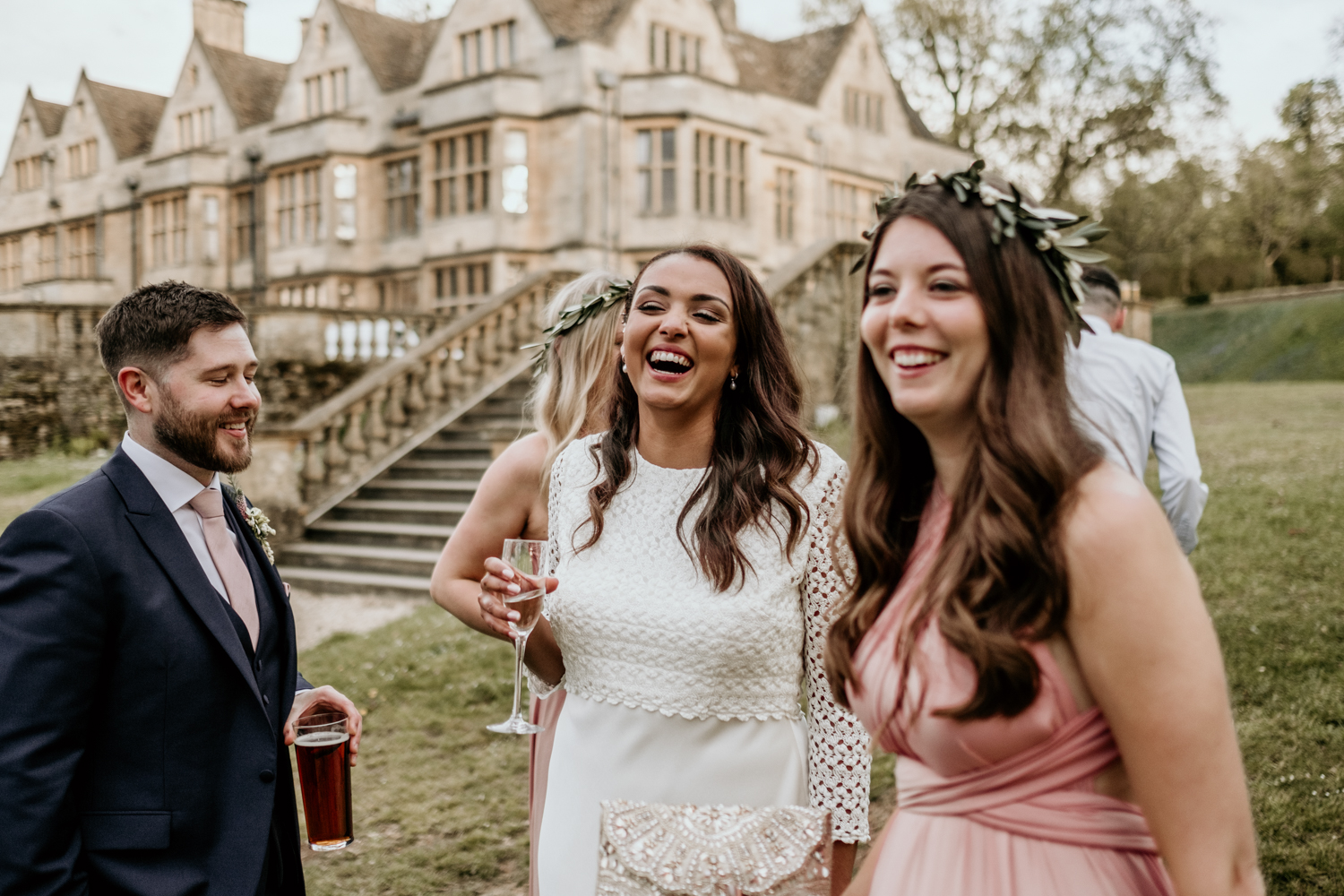 candid shot of bride and guests laughing outside Coombe Lodge Blagdon wedding venue