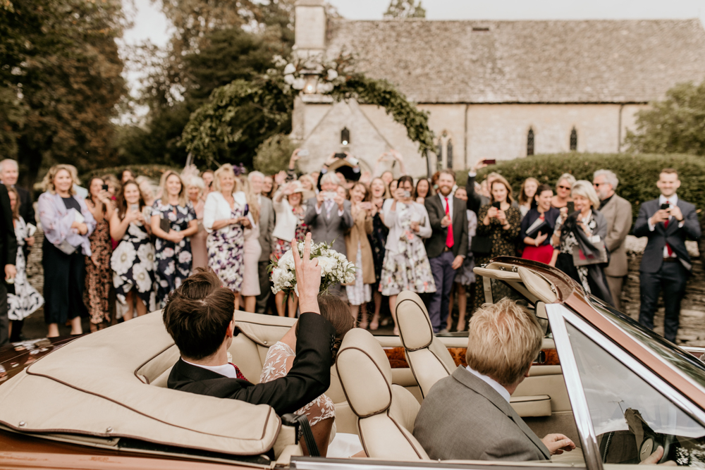 bride and groom waving goodbye to their guests after the church wedding ceremony