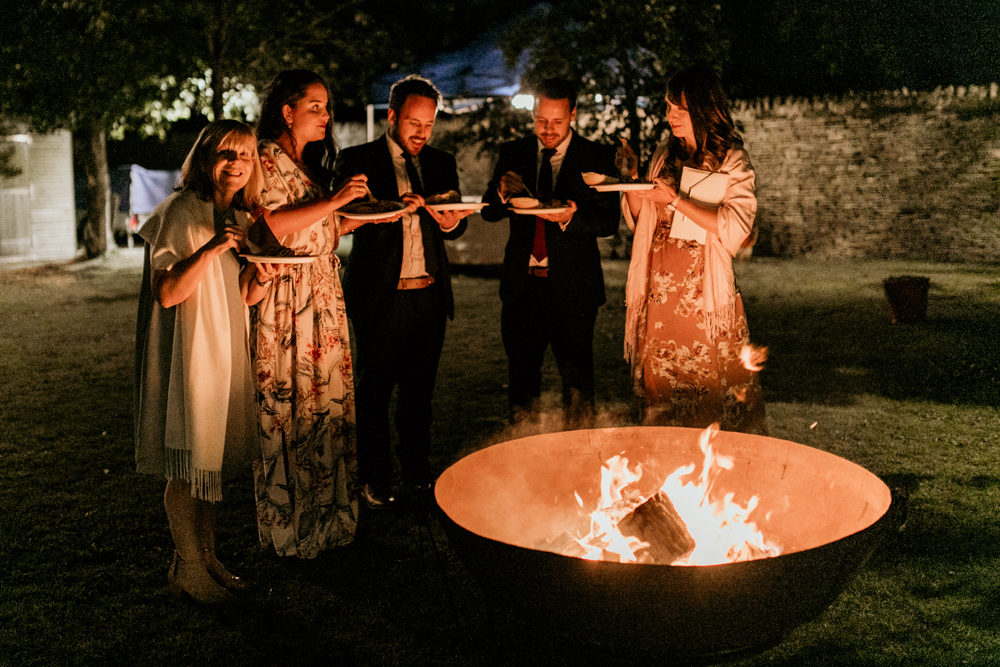 guests eating around huge fire pit for a Poulton wedding
