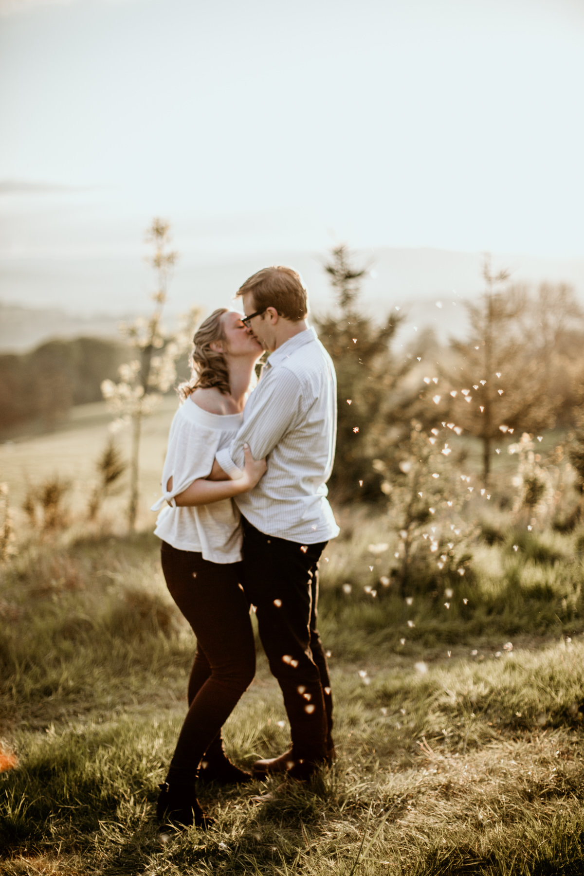 couple kissing on a field during their cotswolds countryside engagement session
