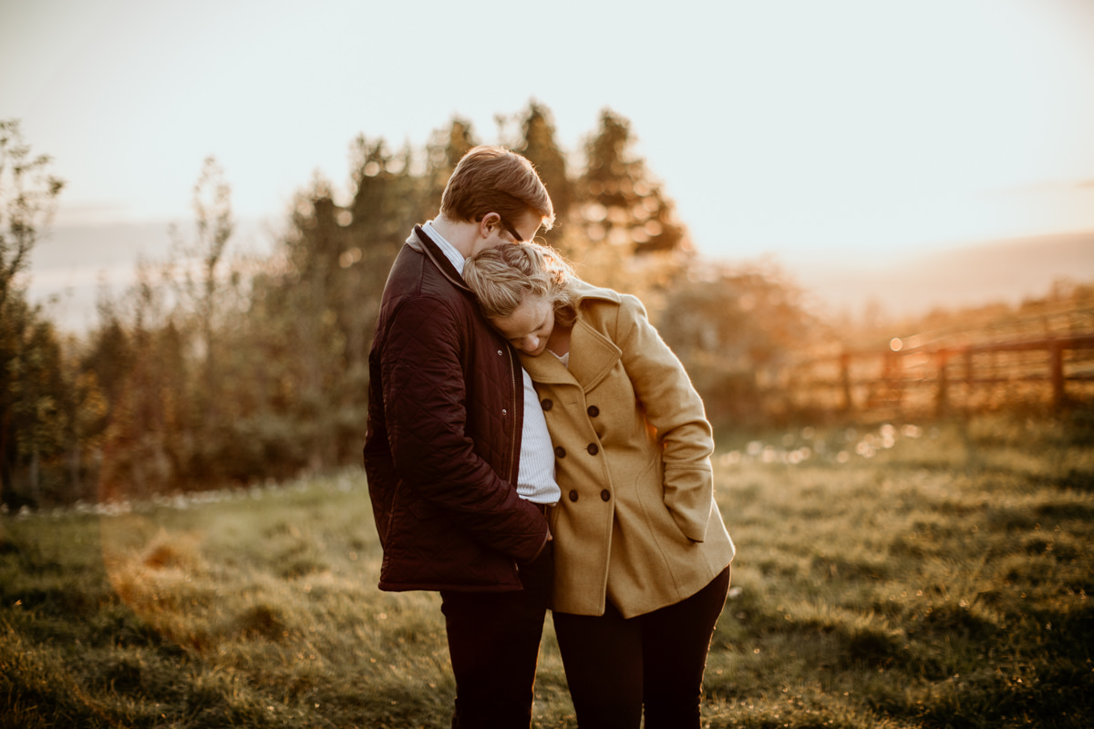 couple holding each other during the golden hour at cotswolds countryside engagement session
