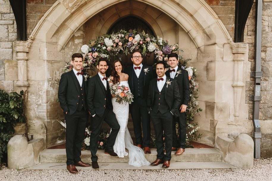 groomsmen group shot in front of a beautiful flower arch at Plas Dinam in Wales