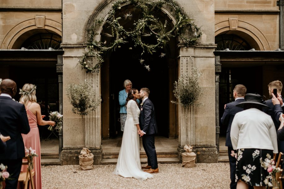 bride and groom first kiss during the outdoor wedding ceremony at Coombe Lodge in Somerset