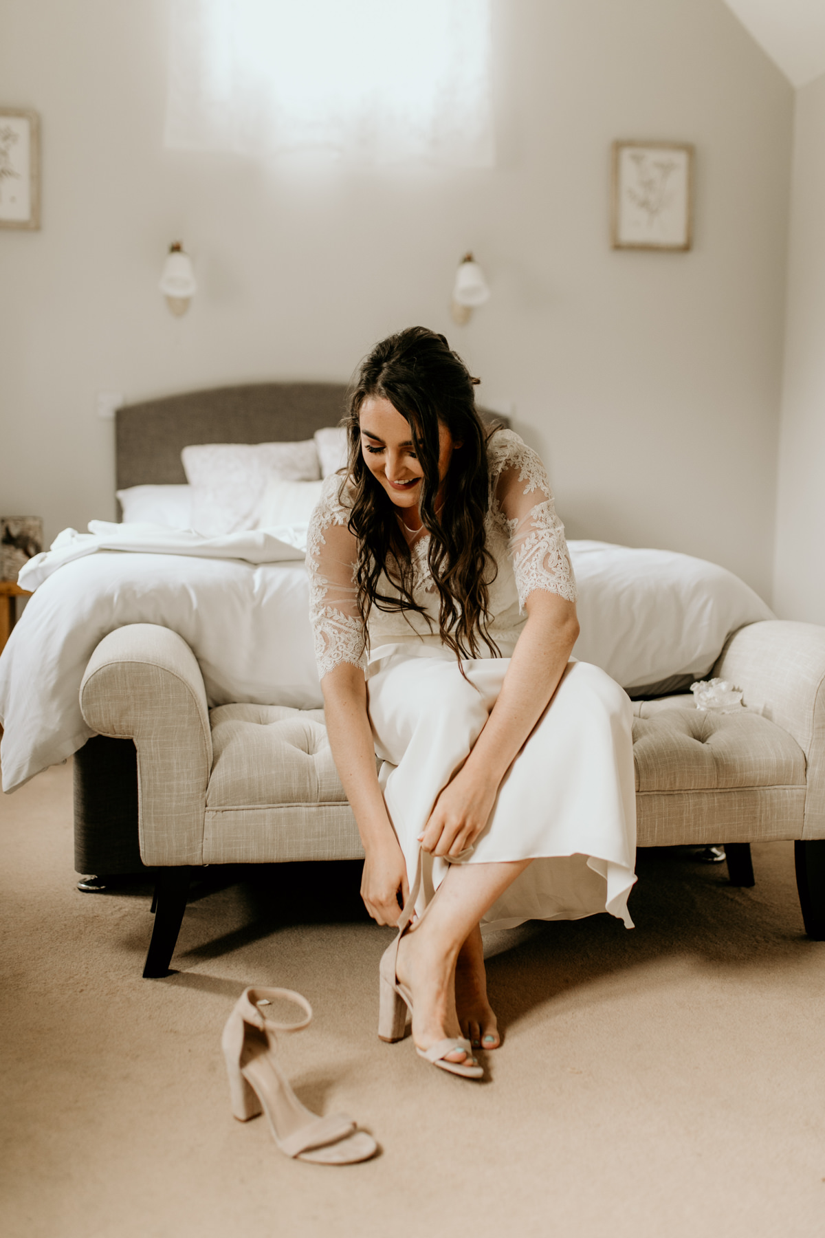 bride getting shoes on before her wedding ceremony in Gloucestershire