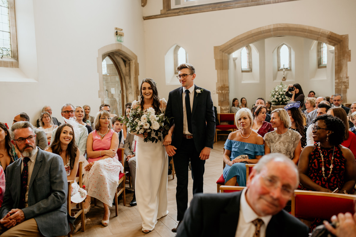 bride walking down the aisle with her brother in church