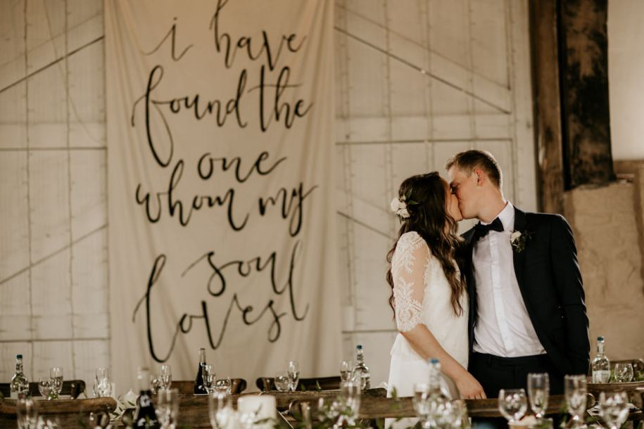 bride and groom kiss at Priors Court Barn with a handwritten large sign behind them