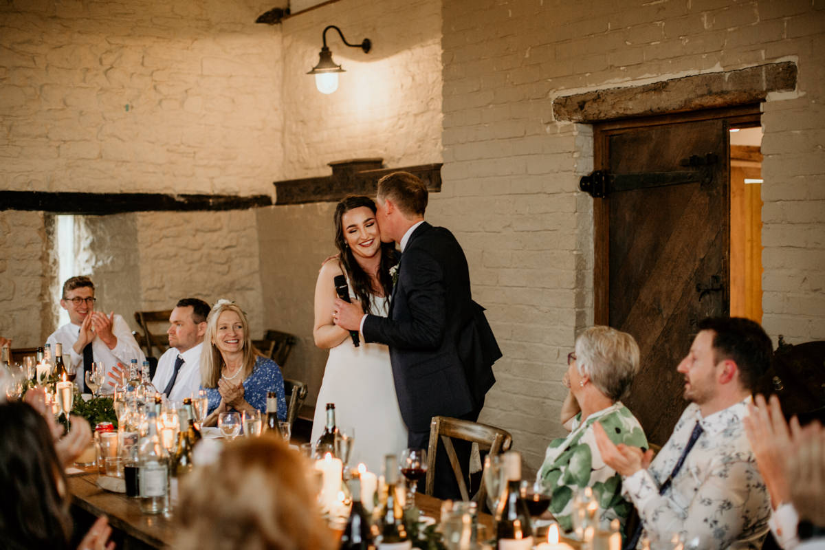 bride and groom kiss during the wedding speeches at Priors Court Barn wedding Gloucester