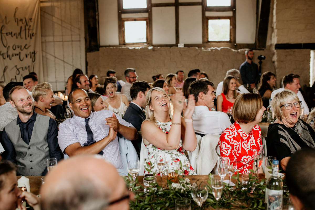 guests laughing during speeches at Priors Court Barn wedding
