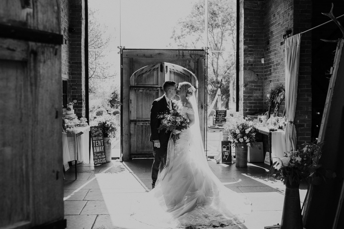 black and white image of bride and groom kiss at Shustoke Barn wedding venue