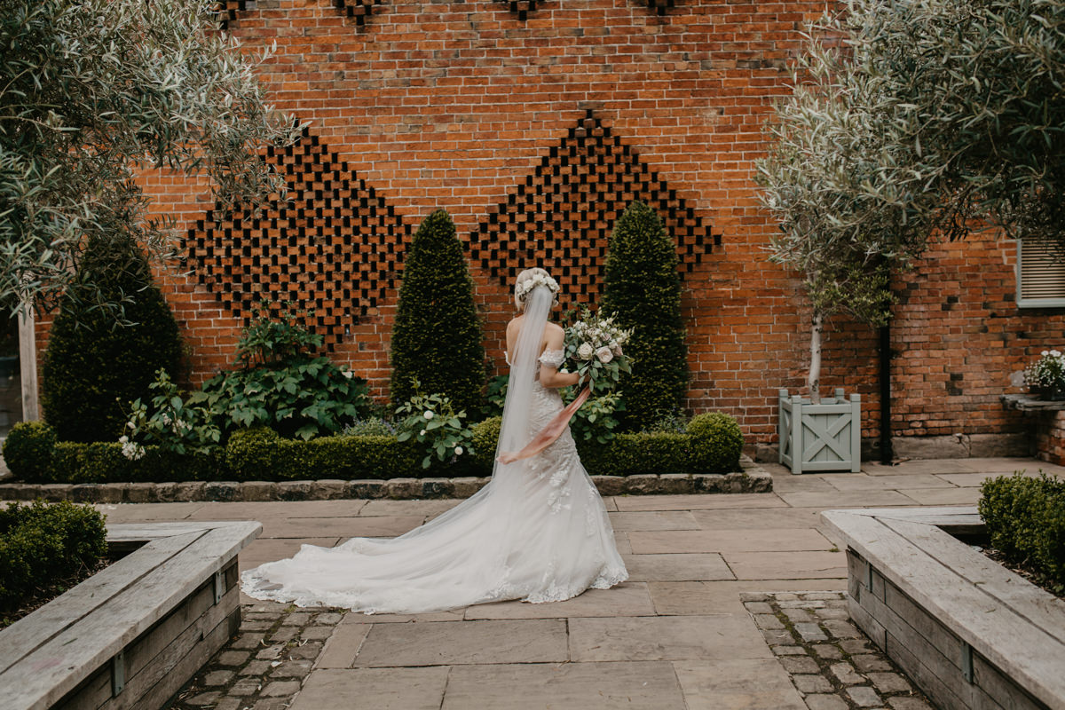 bride walking in the gardens of Shustoke Barn wedding venue