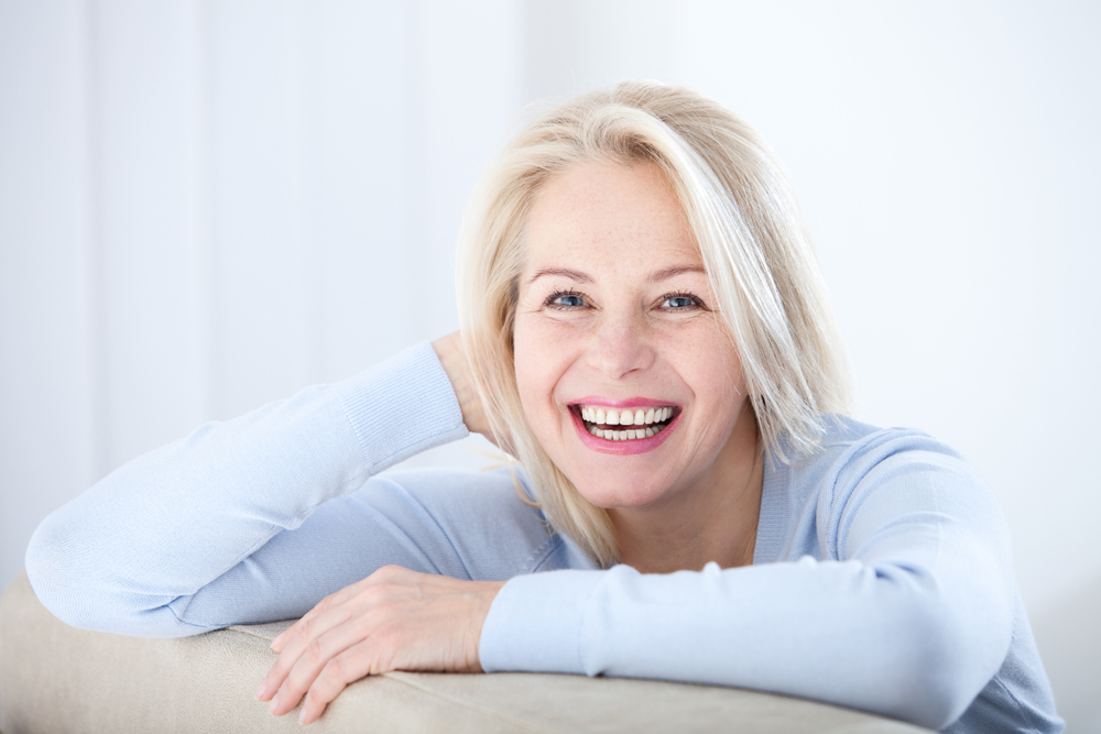 Active beautiful middle-aged woman smiling friendly and looking in camera in living room.
