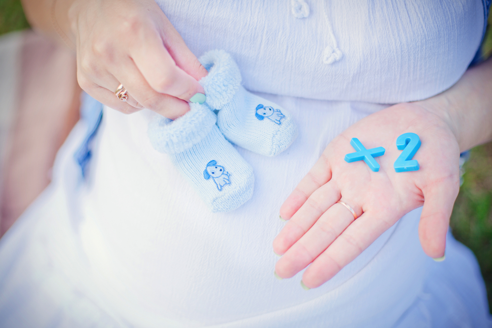 pregnant belly with hands holding shoes and letters that say +2