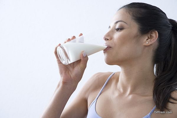 Close-up of a young woman drinking a glass of milk