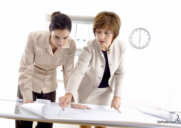 Female architects designing on blueprint at office.