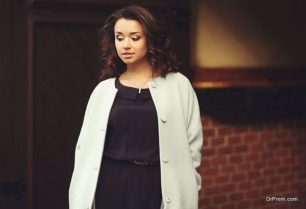 Portrait of beautiful woman in coat looking down