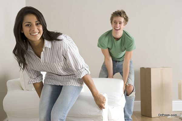 Young Couple Moving Into New Home Carrying Sofa