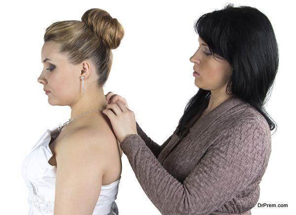 Bridesmade helping bride to wear necklace