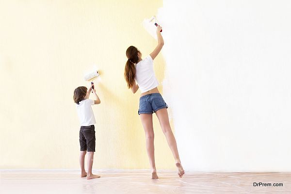 Mother and son painting walls in a new house