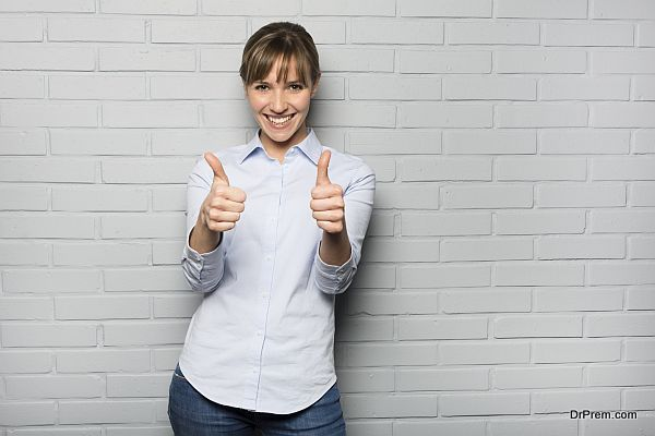Happy Woman Showing Thumbs Up Sign isolated over a wall