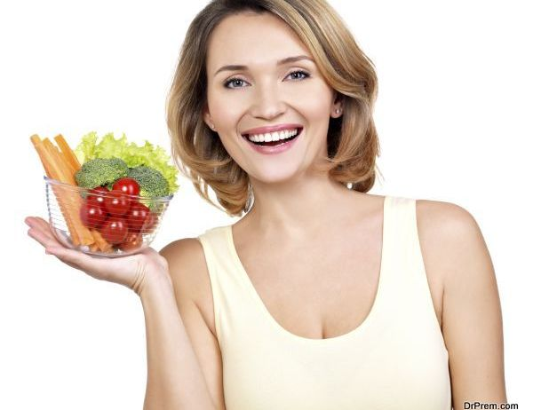 Portrait of a young smiling woman with a plate of vegetables - isolated on white.