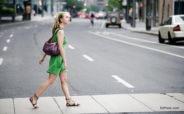 Woman walking in crosswalk in city