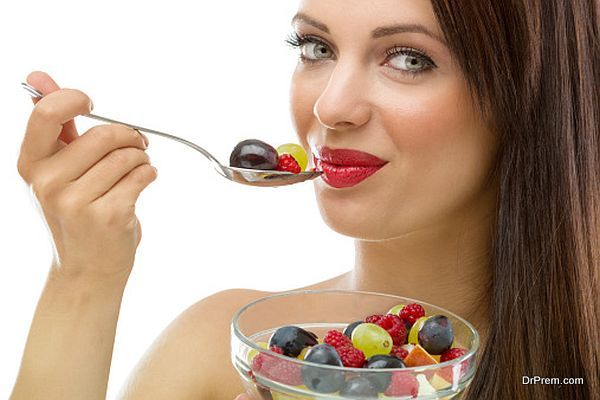 Beautiful young woman eating fresh fruit salad