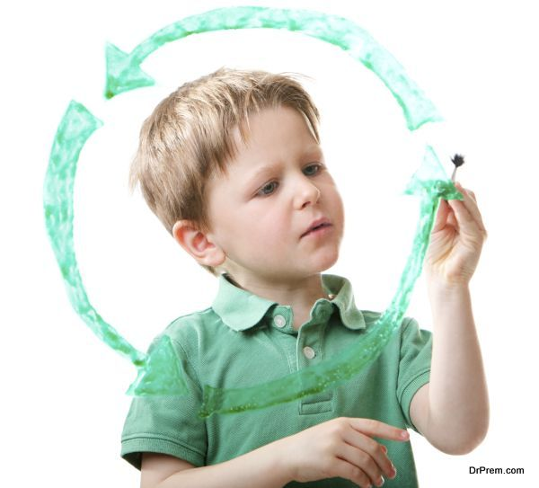 Little boy drawing recycling symbol on glass. Isolated on white.