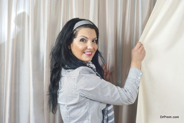 Smiling woman standing at window with curtains and pulling drapes