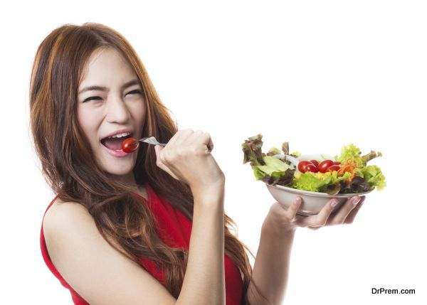 Young asian woman holding and eating fresh vegetable salad on white background
