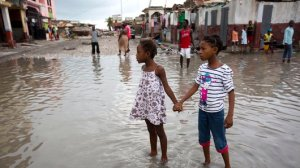 Girls hold hands as they help each other wade through a flooded street after the passing of Hurricane Matthew in Les Cayes, Haiti, Thursday, Oct. 6, 2016. Two days after the storm rampaged across the country's remote southwestern peninsula, authorities and aid workers still lack a clear picture of what they fear is the country's biggest disaster in years. (AP Photo/Dieu Nalio Chery)
