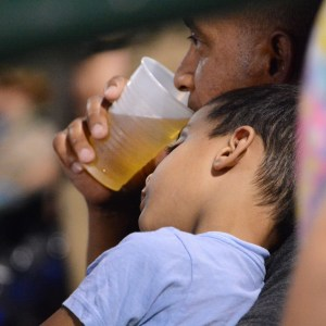 A sleepy child nods off on his fathers shoulder waiting for game play to commence during the Long Island Ducks game against the Bees on Wednesday, July 27, 2016. Photo by Sascha Rosin.