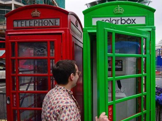 Person stepping inside London SolarBox phone booth charging station