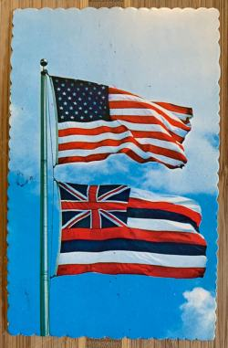 US Flag and Hawaii State Flag flying in front of blue skies