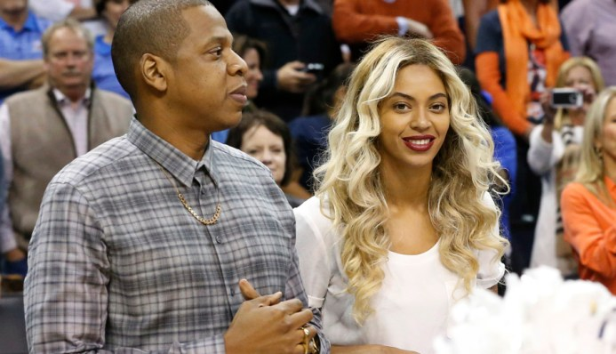 Jay-Z and Beyonce are pictured before the start of an NBA basketball game between the Oklahoma City Thunder and the Los Angeles Clippers in Oklahoma City, Thursday, Nov. 21, 2013. (AP Photo/Sue Ogrocki)